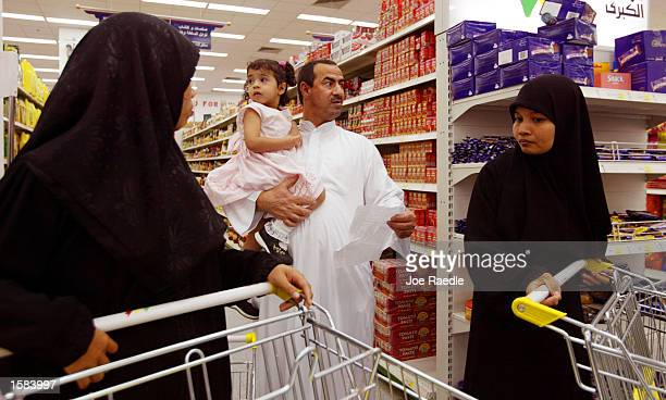 Mohammad Hassan Abbas holds Zahraa Mohammad Hassan Abbes 2 1/2 as he shops with his family for next weeks Ramadan November 2 2002 in Manama Bahrain...