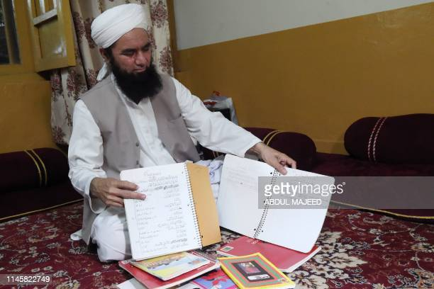 Mohammad Iltimas a Pakistani former religious teacher of American Taliban John Walker Lindh displays school notebooks of Lindh at his residence in...