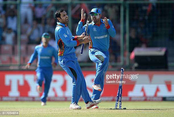 Mohammad Nabi of Afghanistan celebrates with Samiullah Shenwari after running out Joe Root of England during the ICC World Twenty20 India 2016 Group...