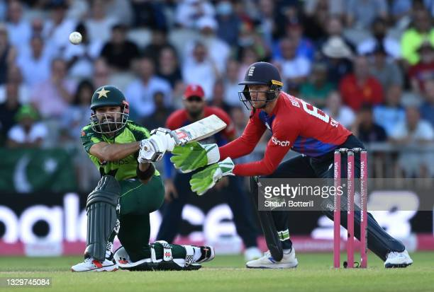 Mohammad Rizwan of Pakistan plays a shot as England wicket keeper Jos Buttler looks on during the third Vitality International T20 match between...