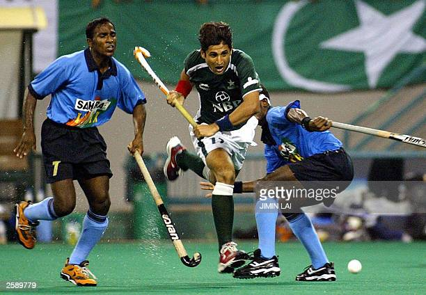 Mohammad Saqlain of Pakistan charges past Vikram Pillay and teammate Ignace Tirkey of India during the finals of the 6th Men''s Asia Cup hockey...