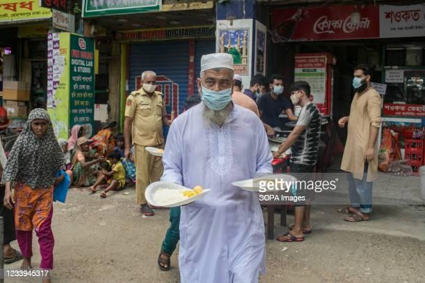 Mohammad Showkat Hossain, owner of Showkat Tehari Ghar distributes lunch among the homeless people during the national wide Covid-19 lockdown.
