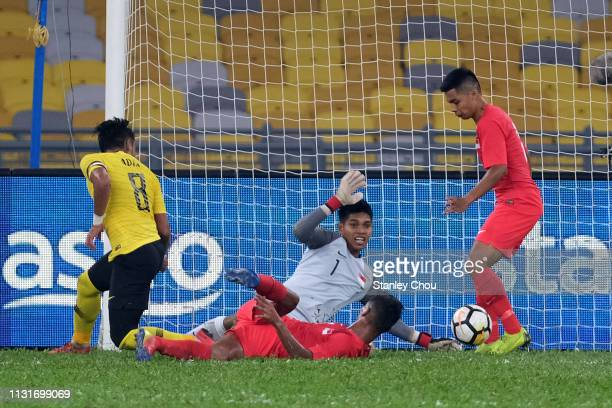 Mohammad Zaquan of Malaysia competes for the ball with Mohamad Izwan of Singapore during the Airmarine Cup match between Malaysia and Singapore at...