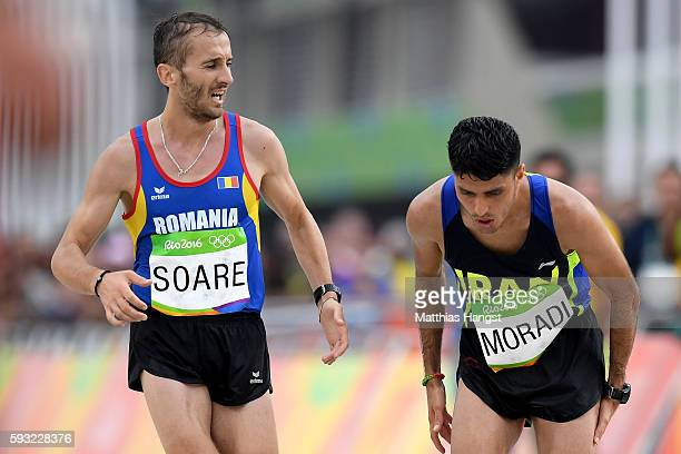 Mohammadjafar Moradi of the Islamic Republic of Iran is assisted by fellow competitor NicolaeAlexandru Soare of Romania during the Men's Marathon on...
