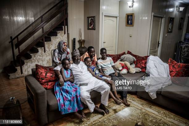 Mohammed Abubakar Bambado the Sarkin Fulani of Lagos watches TV along with his children and his wife after arriving home from work at his house in...