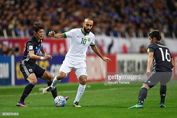 Mohammed Al Sahlawi of Saudi Arabia competes for the ball against Hiroki Sakai and Hotaru Yamaguchi of Japan during the 2018 FIFA World Cup Qualifier...