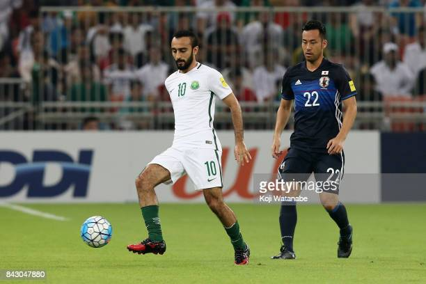 Mohammed Al Sahlawi of Saudi Arabia controls the ball under pressure of Maya Yoshida of Japan during the FIFA World Cup qualifier match between Saudi...