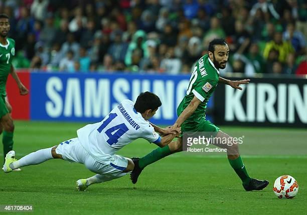 Mohammed Al Sahlawi of Saudi Arabia is challenged by Shukhrat Mukhammadiev of Uzbekistan during the 2015 Asian Cup match between Uzbekistan and Saudi...