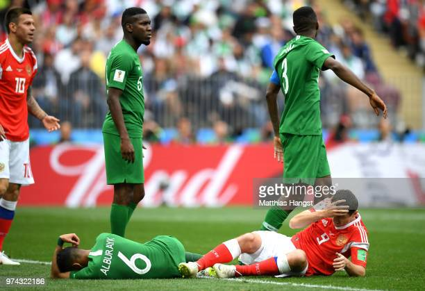 Mohammed Alburayk of Saudi Arabia and Alan Dzagoev of Russia lie on the pitch injured during the 2018 FIFA World Cup Russia Group A match between...