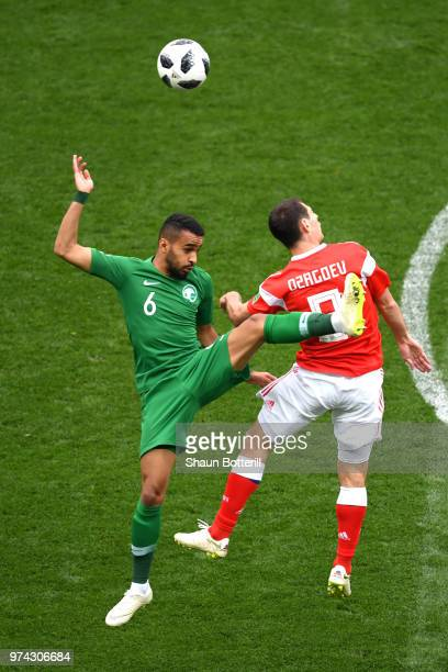 Mohammed Alburayk of Saudi Arabia jumps in the air for the ball with Alan Dzagoev of Russia during the 2018 FIFA World Cup Russia Group A match...