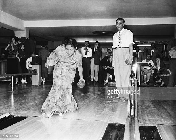 Mohammed Ali Prime Minister of Pakistan who is currently visiting the US is shown watching as his wife the Begum makes a try for the ten pins in a...