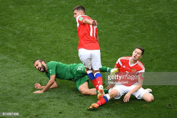 Mohammed Alsahlawi of Saudi Arabia is tackled by Roman Zobnin and Daler Kuziaev of Russia during the 2018 FIFA World Cup Russia Group A match between...