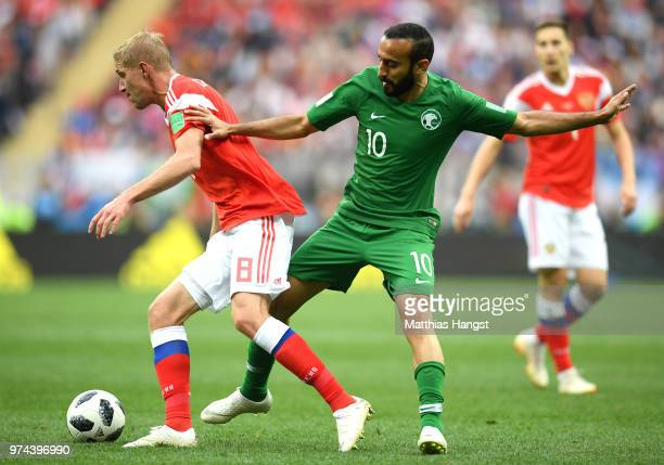 Mohammed Alsahlawi of Saudi Arabia tackels Iury Gazinsky of Russia during the 2018 FIFA World Cup Russia Group A match between Russia and Saudi...
