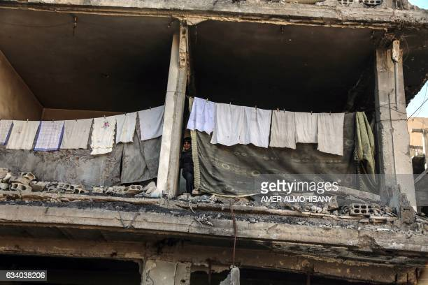 Mohammed al-Zeidalani looks out from behind a washing line in a destroyed building in the rebel-held town of Saqba where his family is taking shelter...