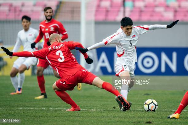 Mohammed Bassim of Palestine and Ri UnChol of North Korea compete for the ball during the AFC U23 Championship Group B match between Palestine and...
