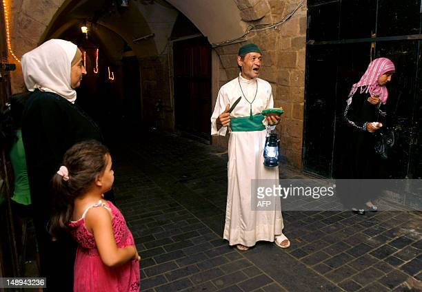 Mohammed Fanas demonstrates on July 19 2012 how he walks through the streets of the Old City in Sidon to wake the sleeping for the 'sohour' meal the...
