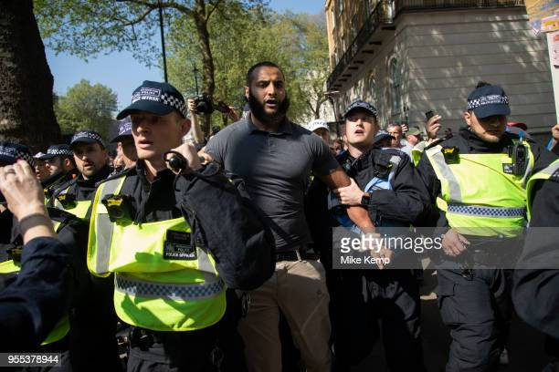 Mohammed Hijab who was originally supposed to speak at the rally is whisked away by police under protection after being set upon at the 'Democratic'...