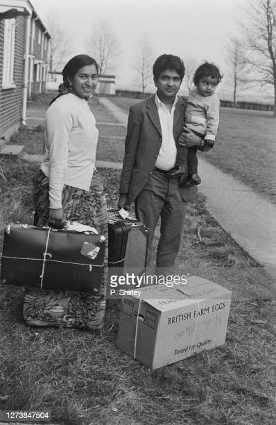 Mohammed Hirani holding a young child in one arm, with the other holding a suitcase, as his wife stands holding a suitcase, with a large box with...