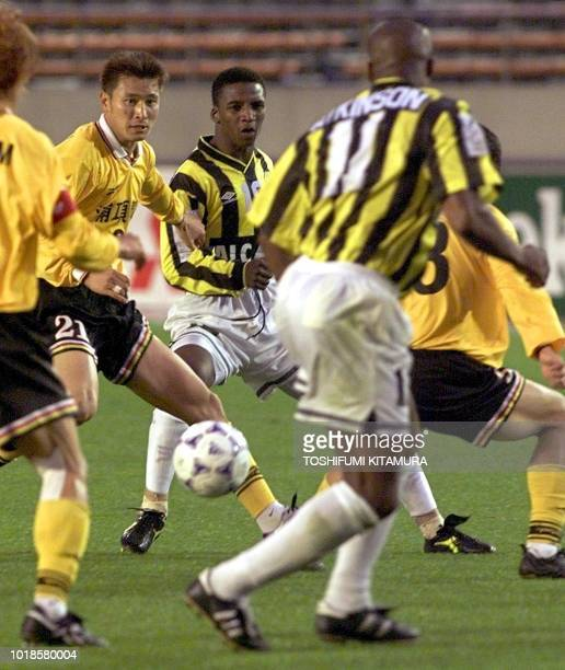 Mohammed MA Hwsawi a midfielder in Saudi Arabia's Al Ittihad passes the ball to forward Dalian R Atkinson amongst defensive players of South Korea's...