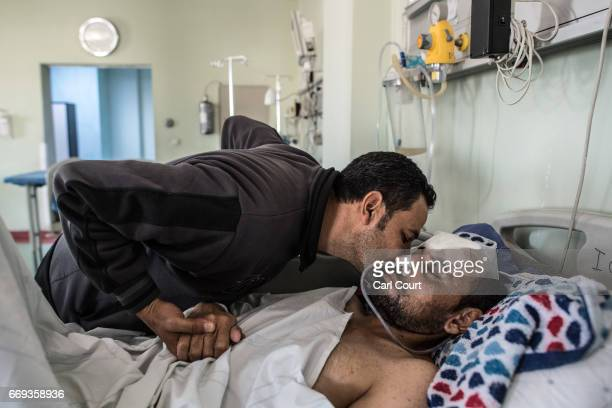 Mohammed Mahmoud who received serious head injuries from shrapnel during an airstrike in Mosul is comforted by his brother Amar Mahmoud while he lies...