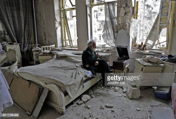 TOPSHOT Mohammed Mohiedin Anis or Abu Omar smokes his pipe as he sits in his destroyed bedroom listening to music on his vinyl player gramophone in...