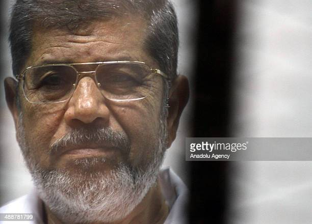 Mohammed Morsi stands inside a defendant's cage during his trial at an eastern Cairo police academy in Cairo Egypt on May 08 2014 An Egyptian court...