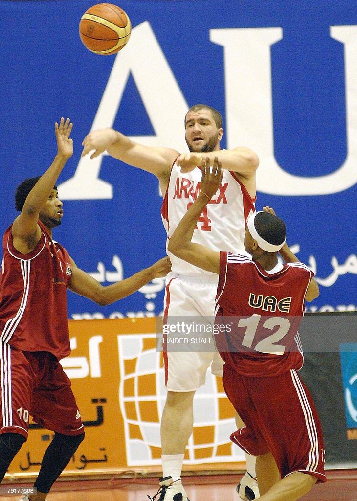 Mohammed Munir al-Kardani of Al-Jazeera club (C) shoots the ball as UAE's Salah Khlefat Abdullah (L) and Rashid Nasser (R) try to stop him during their basketball match for the 19th Dubai International Basketball Championship, 23 January 2008.