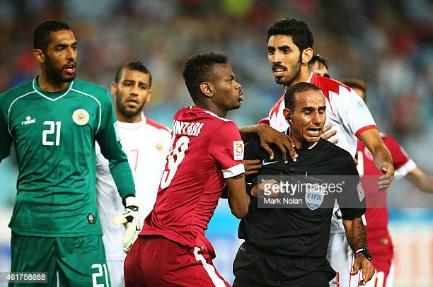 Mohammed Muntari of Qatar reacts after being pushed and is held back by referee Abdullah Mohamed Al Hilali during the 2015 Asian Cup match between...