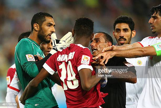 Mohammed Muntari of Qatar reacts after being pushed by Husain Baba Mohamed of Bahrain and is held back by referee Abdullah Mohamed Al Hilali during...