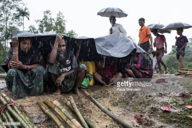 KUTUPALONG BANGLADESH SEPTEMBER 17 Mohammed Nazir and his wife Zohar Nahar hide under a plastic tarp from the monsoon rains that are making life...