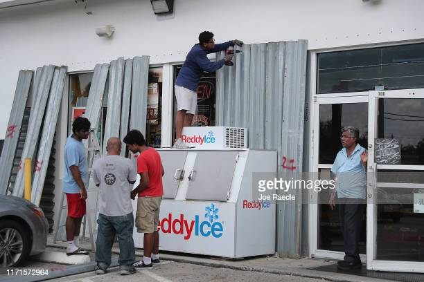 Mohammed Rahman helps place shutters over the windows of a Food Mart store as the owner prepares just in case Hurricane Dorian hits the area on...
