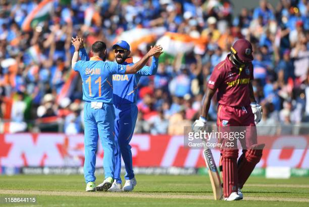 Mohammed Shami of India celebrates after taking the wicket of Shimron Hetmyer of West Indies with Virat Kohli of India during the Group Stage match...