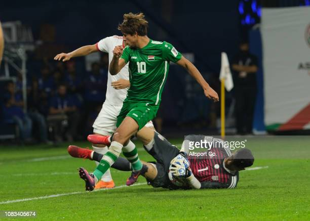 Mohannad Ali of Iraq tackles Alireza Beiranvand of Iran during the AFC Asian Cup Group D match between Iran and Iraq at Al Maktoum Stadium on January...