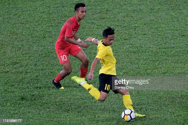 Mohd Nor Azam of Malaysia competes for the ball with Muhammad Faris Ramli of Singapore during the Airmarine Cup match between Malaysia and Singapore...