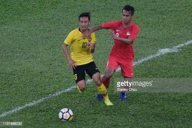 Mohd Nor Azam of Malaysia competes for the ball with Shahdan Sulaiman of Singapore during the Airmarine Cup match between Malaysia and Singapore at...
