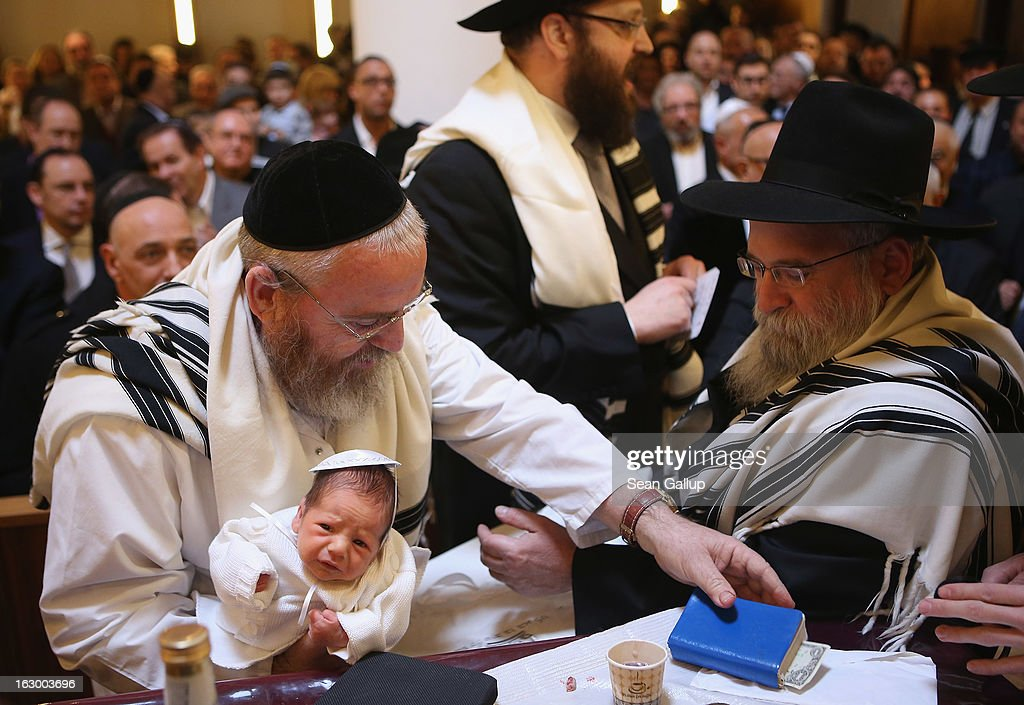 Mohel Manachem Fleischmann (L) concludes the circumcision ceremony of baby infant Mendl Teichtal at the Chabad Lubawitsch Orthodox Jewish synagogue on March 3, 2013 in Berlin, Germany. Germany's parliament, the Bundestag, passed a law affirming the legality of circumcision in December after a Cologne court called the practice into question in May of 2012, a ruling that sparked outrage among Germany's Jewish and Muslim population.