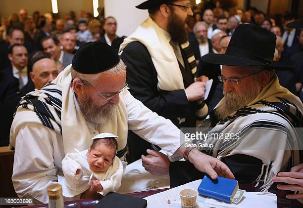 Mohel Manachem Fleischmann concludes the circumcision ceremony of baby infant Mendl Teichtal at the Chabad Lubawitsch Orthodox Jewish synagogue on...