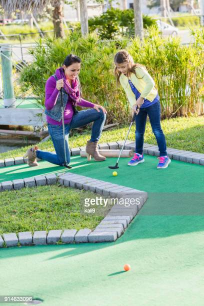moher and daughter playing miniature golf - miniature golf stock photos and pictures