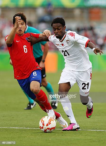 Mohsin Al Khaldi of Oman and Ro Hak Su of Korea Republic contests possession during the 2015 Asian Cup match between Korea Republic and Oman at...