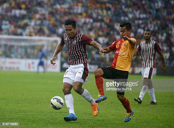 Mohun Bagan Dhanachandra Singh is tackled by East Bengal's Sanju Pradhan during an ILeague football match at The Kanchenjungha Stadium in Siliguri on...