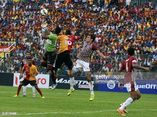 Mohun Bagan's goalkeeper Debjit Majumderis watched by teammate Luciano Sobrosa as he fights for the ball with East Bengal's Ranti Martinsduring an...