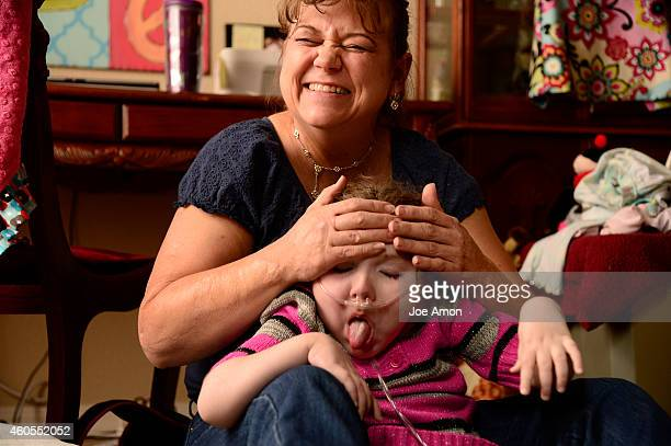 October 03: Moina Matthias, an occupational therapist from Rehab for All in Colorado Springs, working with Haleigh on stretching and smiling. She...