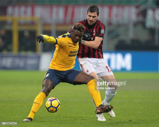 Moise Kean of Hellas Verona competes for the ball with Alessio Romagnoli of AC Milan during the Tim Cup match between AC Milan and Hellas Verona FC...