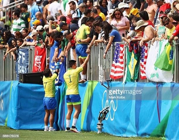 Moises Duque of Brazil climbs into the stand to embrace fans after the Men's Rugby Sevens placing 1112 match between Brazil and Kenya on Day 6 of the...