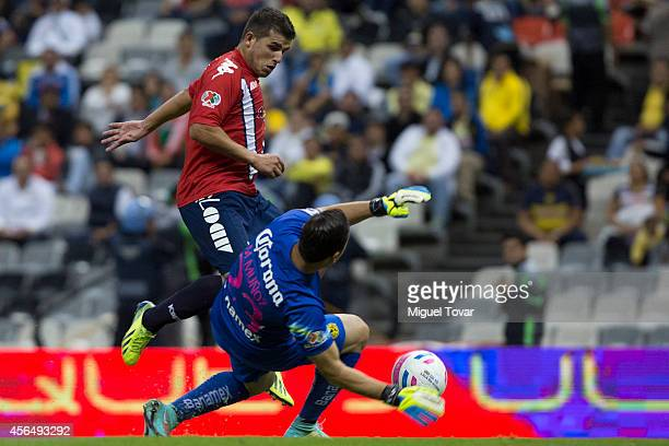 Moises Munoz goalkeeper of America tries to block the chance of scoring of Liber Quinones of Veracruz during a match between America and Veracruz as...