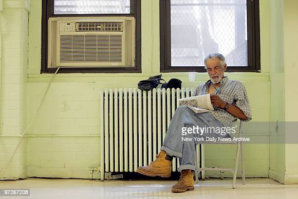 Moises Rios of East Harlem finds a nice spot near a large air conditioner to read a paper as he escapes the heat at the Leonard Covello Senior Center...