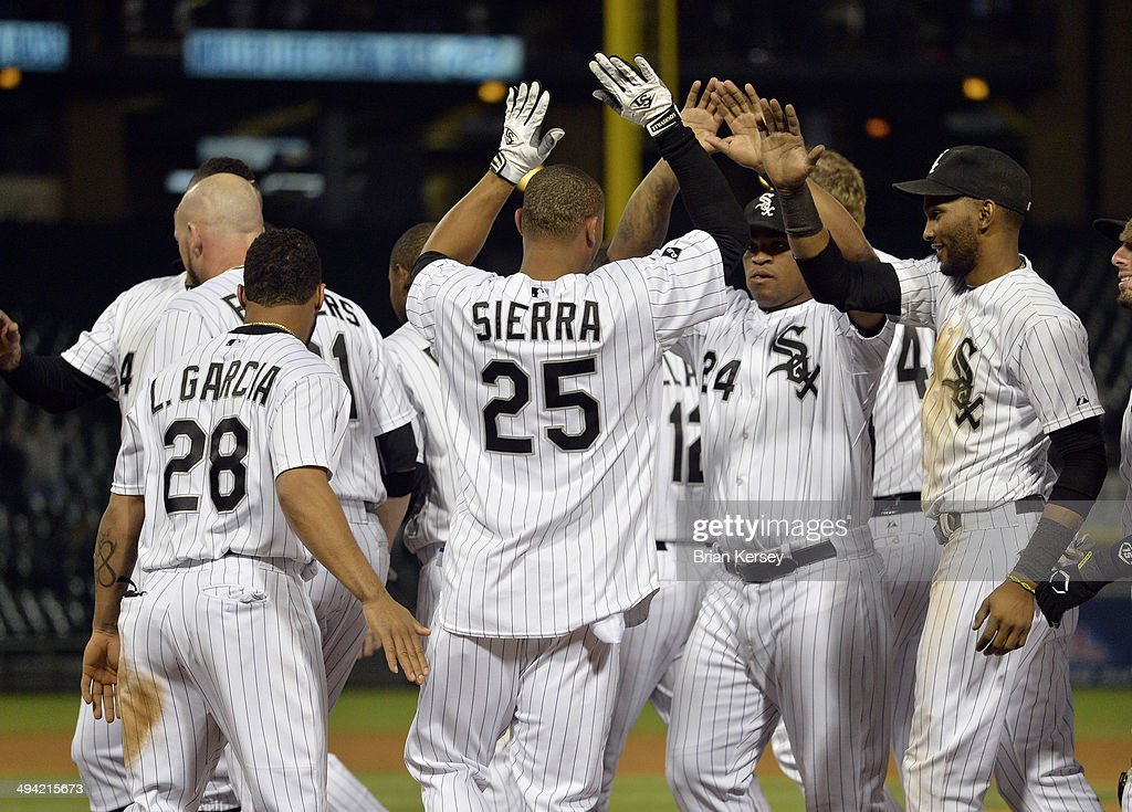 Moises Sierra #25 of the Chicago White Sox is congratulated by teammates Leury Garcia #28, Dayan Viciedo #24 and Alexei Ramirez #10 (R) after hitting a game-winning RBI single scoring Garcia during the ninth inning against the Cleveland Indians at U.S. Cellular Field on May 28, 2014 in Chicago, Illinois. The White Sox defeated the Indians 3-2.