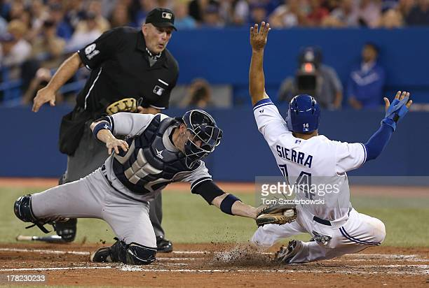 Moises Sierra of the Toronto Blue Jays is tagged out at home plate in the fifth inning during MLB game action as Chris Stewart of the New York...