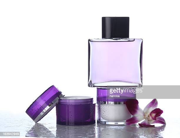Moisturizers and perfume on white with orchid