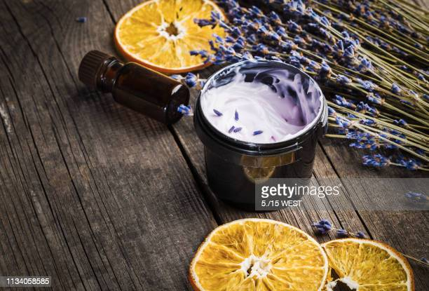 moisturizing cream organic with a lavender and orange dry on a wooden table - cosmetics stock pictures, royalty-free photos & images
